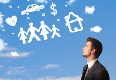 Businessman daydreaming with family and household clouds Royalty Free Stock Images
