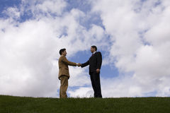 Businessman deal. Two businessman making a deal with a handshake at the field Stock Photo