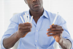 Businessman deciding between electronic or normal cigarettes Royalty Free Stock Photo