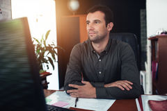 Businessman deep in thought at his desk Royalty Free Stock Photography
