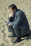 Businessman deep in thought on the sand Royalty Free Stock Image