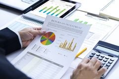 Reviewing a financial report in returning on investment analysis Stock Images