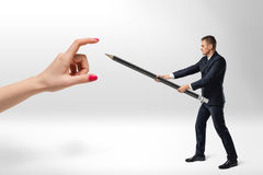 Businessman defending himself from woman's hand with big pencil Royalty Free Stock Photography