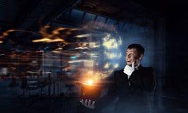 Businessman demonstrating magic . Mixed media Stock Photo