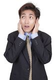 Businessman in denial not listening. Standing oriental Chinese young businessman covering his ears in denial of reality and deaf for corporate and business facts Stock Image