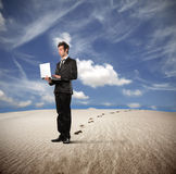 Businessman in a desert Stock Images
