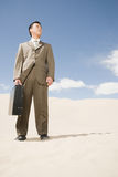 Businessman in the desert Stock Images