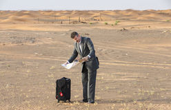 Businessman in  a desert with a suitcase, looking at a map Royalty Free Stock Image