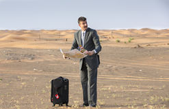 Businessman in  a desert with a suitcase, looking at a map Stock Images