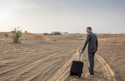 Businessman in  a desert with a suitcase Stock Images