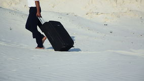 Businessman in desert. A young man in a business suit and a large luggage bag in the desert. Businessman on the road to stock video