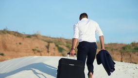 Businessman in desert. A young man in a business suit and a large luggage bag in the desert. Businessman on the road to stock footage