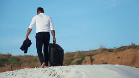 Businessman in desert. A young man in a business suit and a large luggage bag in the desert. Businessman on the road to stock video footage