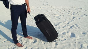 Businessman in desert. A young man in a business suit and a large luggage bag in the desert. Businessman on the road to. A young man in a business suit without stock footage