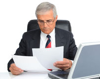 Businessman at desk with computer and papers Stock Images