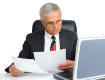 Businessman at desk with computer and papers Stock Image