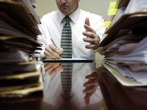 Businessman at Desk with Files Gesturing Stock Images