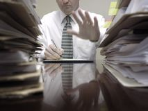 Businessman at Desk with Files Holding up Hand Royalty Free Stock Photography