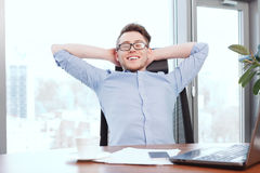 Businessman at desk with hands behind his head Stock Image