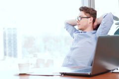 Businessman at desk with hands behind his head Stock Photos