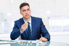 Businessman at desk holding money with worried face expression Royalty Free Stock Photo