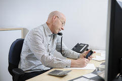 Businessman at desk on phone. Caucasian middle-aged businessman sitting at desk in office talking on telephone Royalty Free Stock Images