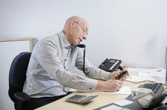 Businessman at desk on phone. Caucasian middle-aged businessman sitting at desk in office talking on telephone Stock Photos