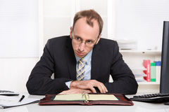 Businessman at desk with problems, stress and overworked sitting. In his office - burnout stock photography
