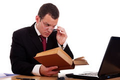Businessman on desk reading and studying Stock Photography