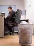 Businessman at desk and trash basket Stock Image