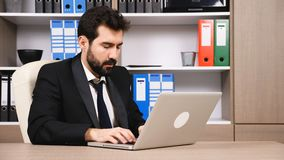 Businessman at the desk typing angry a reply to an email. Business and finance. Long work hours stock video footage