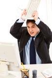 Businessman destroying computer using keyboard Royalty Free Stock Photos