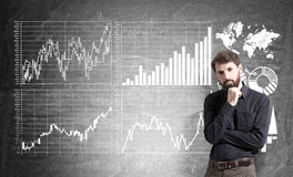 Businessman and diagrams on wall Royalty Free Stock Photos
