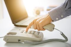 Businessman dial digital telephone with office background Stock Image