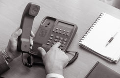 The businessman dials the number on the landline phone Royalty Free Stock Photos