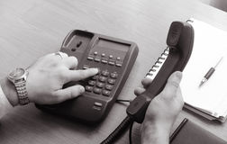 The businessman dials the number on the landline phone, holds the handset in his right hand Stock Image