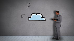 Businessman with diary watching animated electronic devices circling cloud. On grey wall stock video