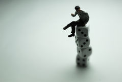 Businessman on Dice. A businessman sat on top of some dice Stock Image