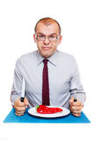 Businessman on a diet. Eating raw red pepper isolated on white background Royalty Free Stock Images