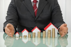 Businessman With Different Houses And Stacks Of Coins. Close-up Of Businessman Hand Near Different Size Houses And Stacks Of Coins On Table stock photo