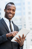 Businessman from digital age. Cheerful young African man in formalwear working on digital tablet and smiling while standing outdoors stock photos