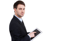 Businessman from digital age. Confident young man in formalwear working on digital tablet and looking at camera while standing isolated on white royalty free stock photography