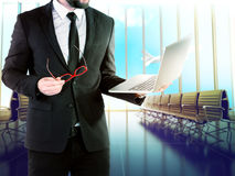 Businessman with digital notebook on blurred background airport. Stock Images
