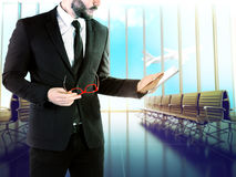 Businessman with digital tablet on blurred background airport. Stock Image