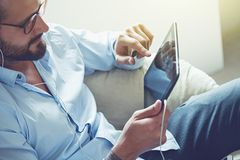 Businessman with tablet and earphones stock image