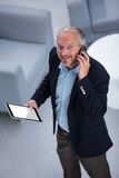 Businessman with digital tablet looking up while talking on his phone Royalty Free Stock Images
