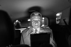 Businessman with a digital tablet sitting in the back seat of a car Stock Photos