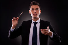 businessman directing with a conductor's stick Stock Photography