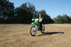 Businessman on Dirt Bike. Thrity something business man in suit riding dirt bike on dirt riding track Stock Images