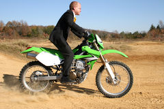 Businessman on Dirt Bike. Thrity something business man in suit riding dirt bike on dirt riding track Royalty Free Stock Photography